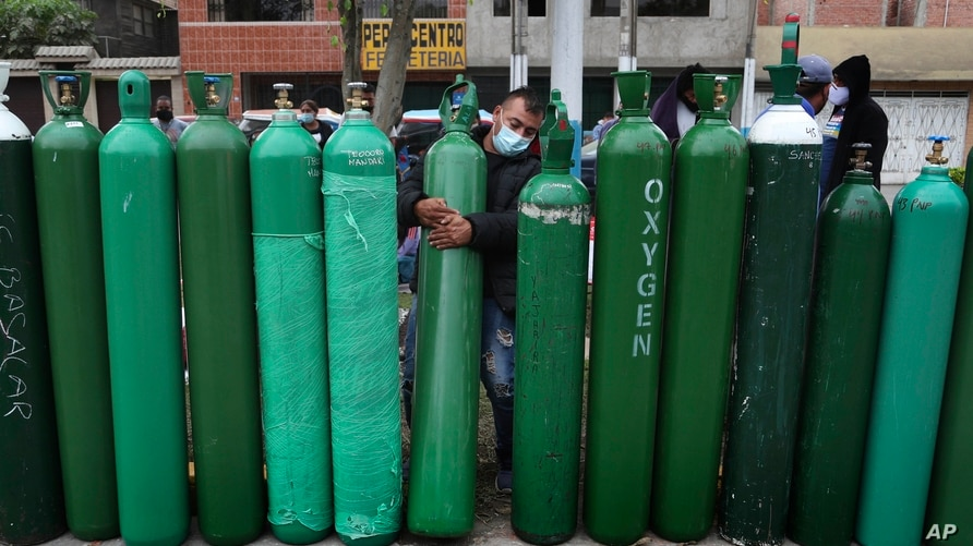 Edgar Barbaran exchanges a small, empty oxygen tank for a large one as he waits since the previous day for a refill shop to open in Callao, Peru, amid the COVID-19 pandemic.