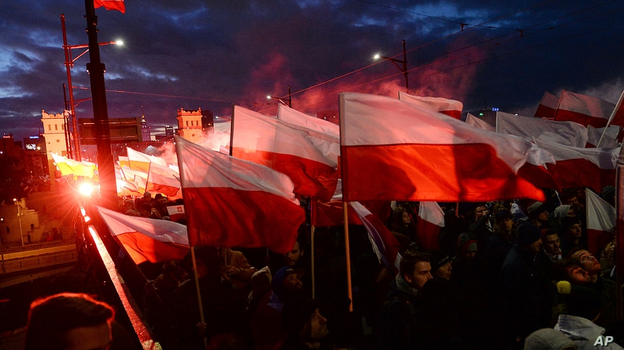 FILE - Demonstrators burn flares and wave Polish flags during an annual march to mark Poland's National Independence Day, in Warsaw, Poland, Nov. 11, 2017.