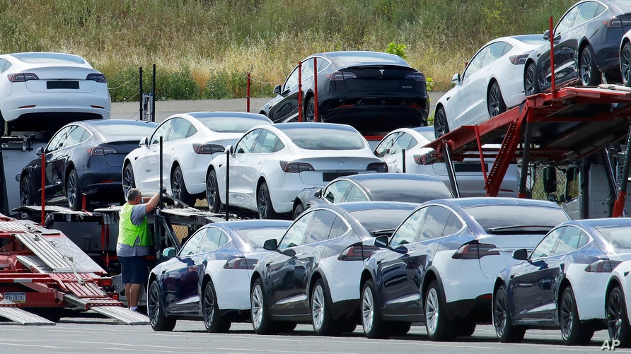 FILE - Tesla cars are loaded onto carriers at the Tesla electric car plant in Fremont, California, May 13, 2020. The Biden adminstration has made short-term emission reductions a top priority.