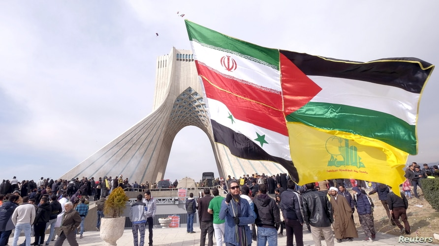 FILE - A man carries a giant banner comprising the flags of Iran, Syria, the Palestinian territories and Hezbollah, during a ceremony marking the 37th anniversary of the Islamic Revolution, in Tehran, Febr. 11, 2016.