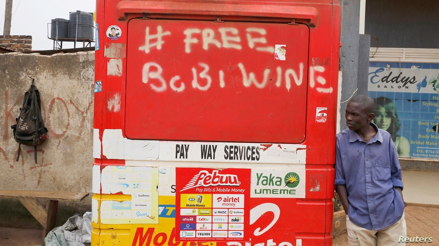 A man leans on a closed kiosk with graffiti calling to free Ugandan opposition presidential candidate Bobi Wine, in Kampala, Uganda, Jan. 17, 2021.