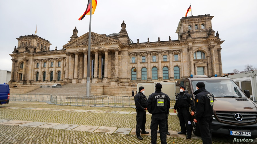 FILE -Police officers stand outside the Reichstag building, seat of Germany's lower house of parliament in Berlin, Nov. 18, 2020.