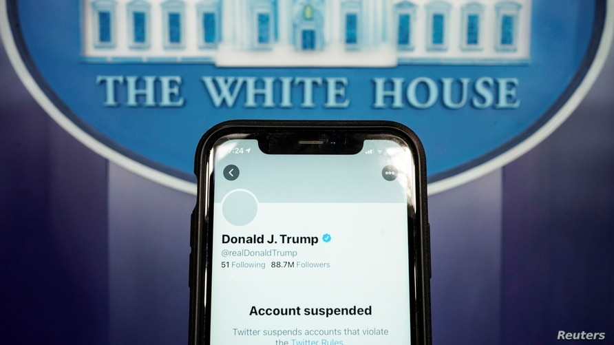 A photo illustration shows the suspended Twitter account of U.S. President Donald Trump on a smartphone at the White House briefing room in Washington, D.C., Jan. 8, 2021.