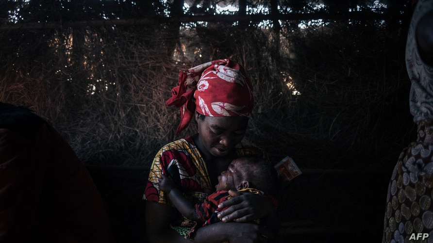 A displaced woman cares for her child who suffers from acute diarrhoea in the makeshift health center of the internally…