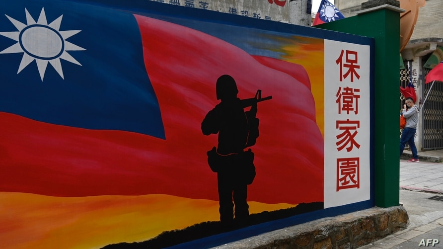 This photo taken on October 21, 2020 shows a tourist (R) walking past a mural painted on a wall on Taiwan's Kinmen islands,…