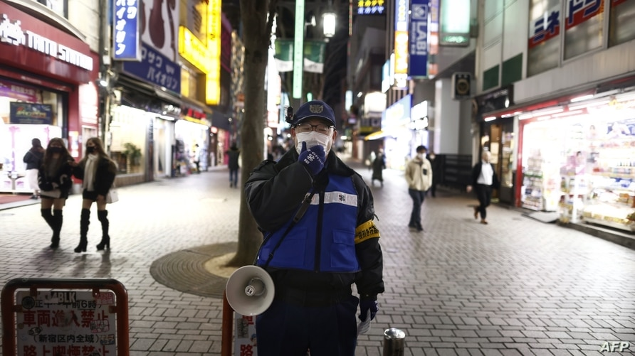 A police officer asks people to refrain from going out after 8pm in the Shinjuku area of Tokyo on January 8, 2021 during the…