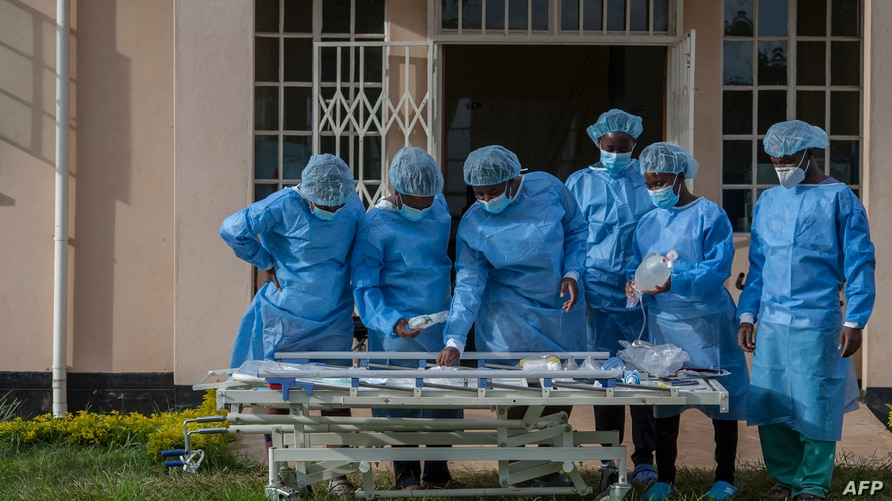 Medical personnel dressed in personal protective equipment are seen at a lodging building readying for their turn to go and…