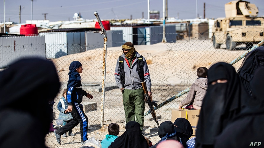 A member of Kurdish internal security stands guard as Women lead children ahead of departure during the release of another…