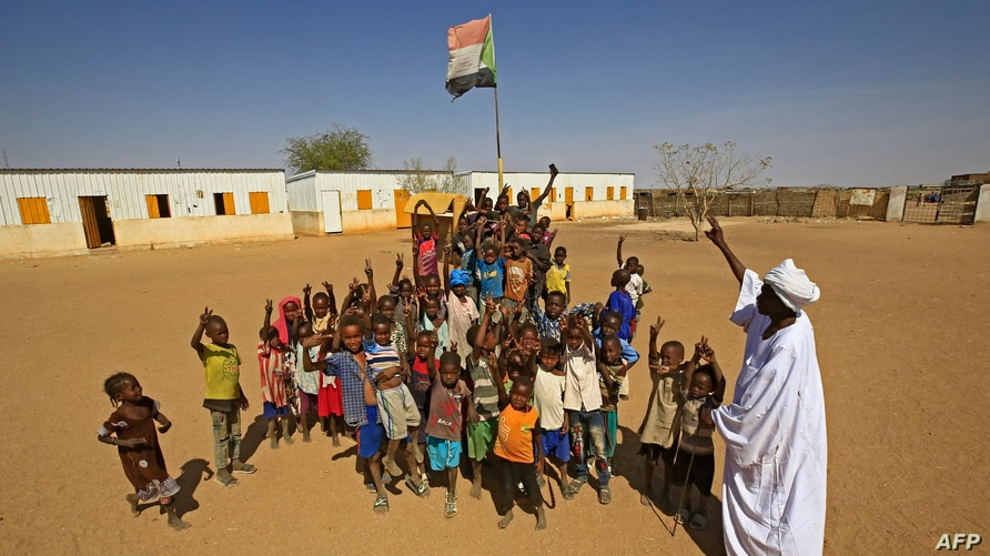 Displaced Sudanese children gather under the national flag in a school yard in the Otash internally displaced people's camp on…