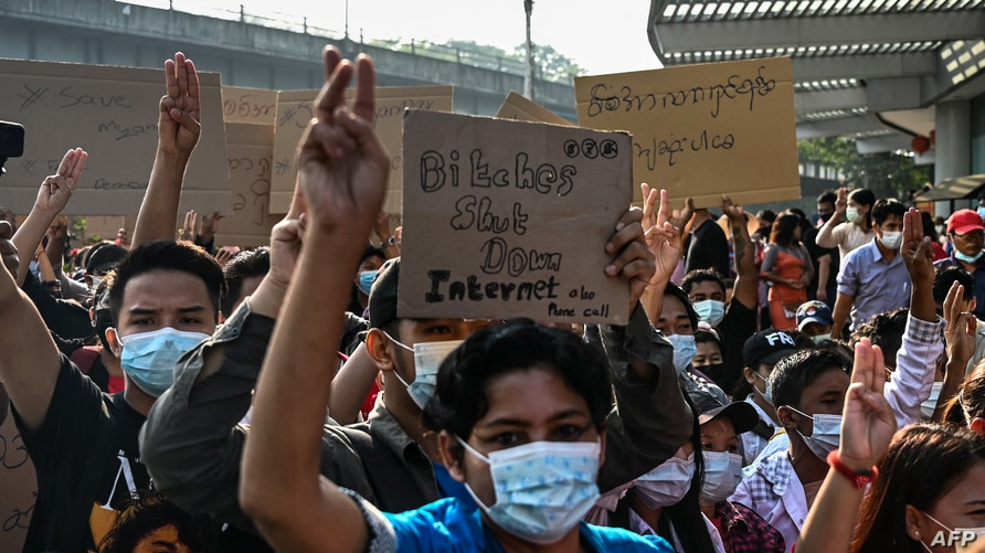 Protesters hold up the three finger salute and placards denouncing the move to shut down internet access during a demonstration…