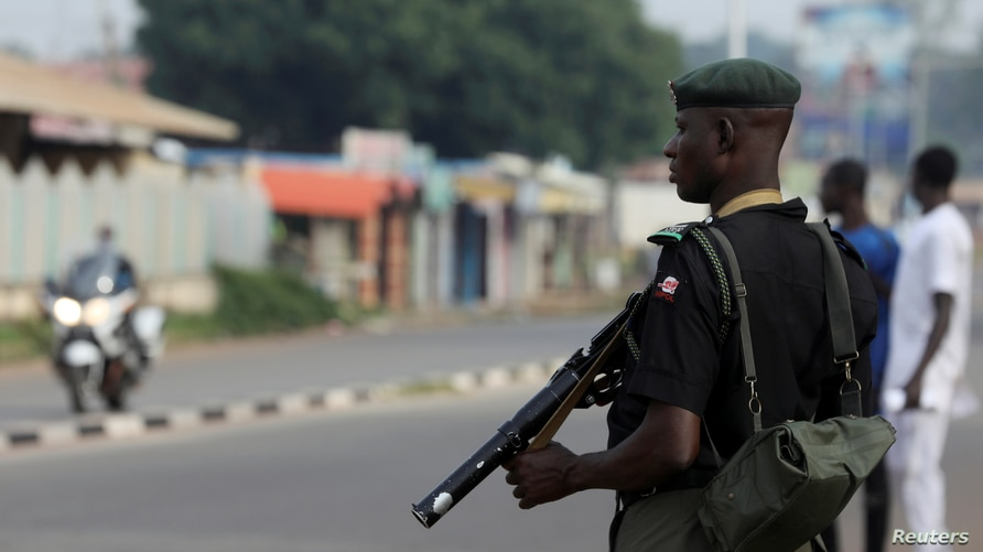 A member of security forces stands guard outside a court in the northern city of Kaduna, Nigeria October 4, 2018. REUTERS…