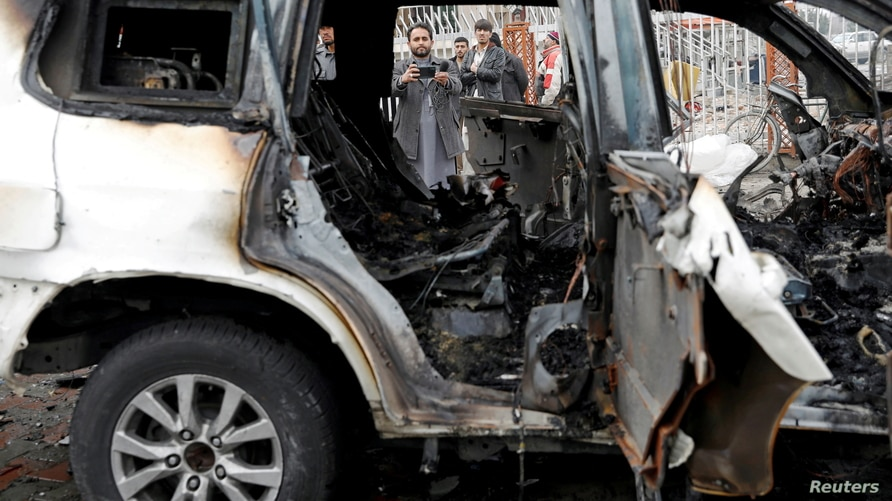 FILE - An Afghan journalist films a damaged vehicle at the site of a blast in Kabul, Afghanistan, Dec. 20, 2020.