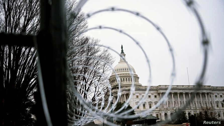 FILE PHOTO: Barbed wire and security fencing surrounds the U.S. Capitol in Washington, U.S., January 26, 2021. REUTERS/Al Drago…