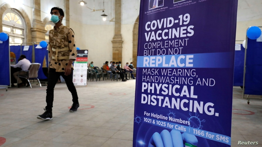 A man walks past an awarness sign inside the Khaliq Dina Hall and Library, which has been converted to be used as a vaccination…