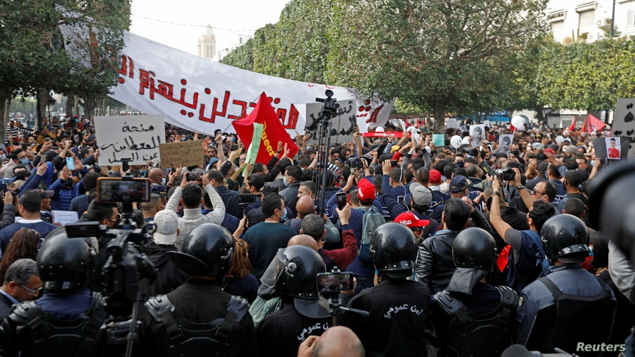 Demonstrators attend a protest to mark the anniversary of a prominent activist's death and against allegations of police abuse, in Tunis, Tunisia, Feb. 6, 2021.