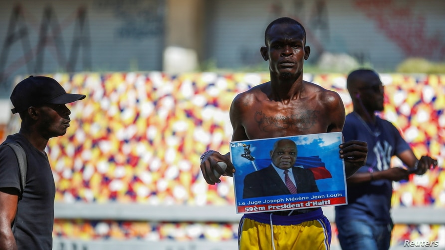 A man holds a photograph of Supreme Court Judge Joseph Mecene Jean-Louis during protests against Haiti's President Jovenel…