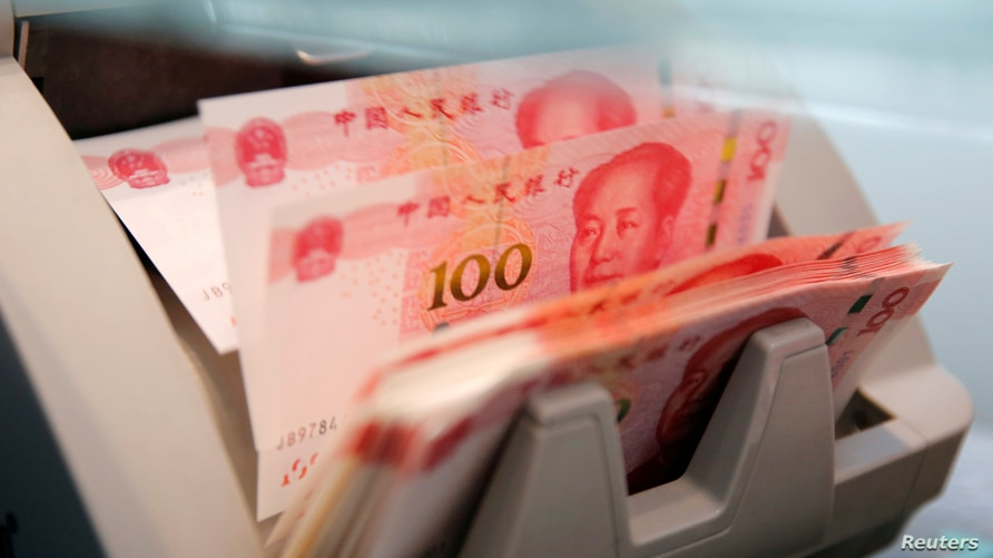 FILE PHOTO: Chinese 100 yuan banknotes are seen in a counting machine while a clerk counts them at a branch of a commercial…