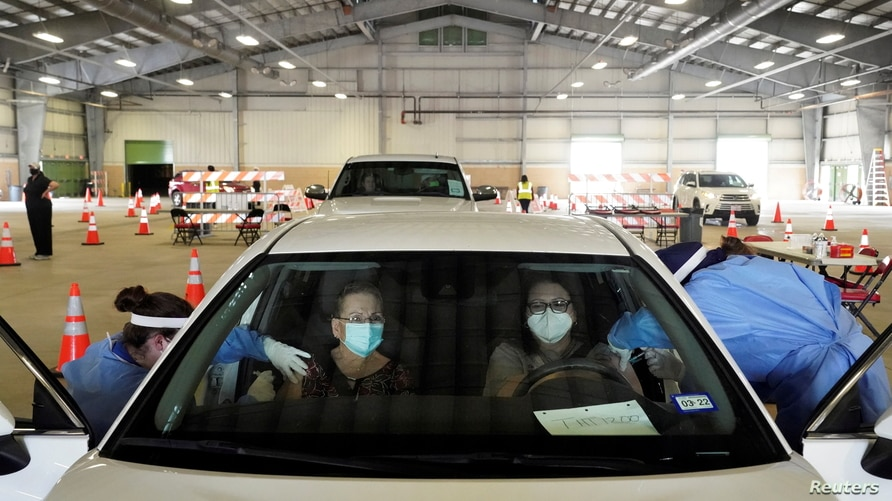 Eva Martinez and Sandra Vaden  receive vaccination against coronavirus disease (COVID-19) at a drive-through site in Robstown,…