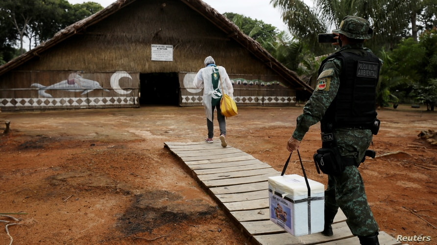 A municipal health worker and an environmental military police officer carry the AstraZeneca/Oxford vaccine as they enter in an…