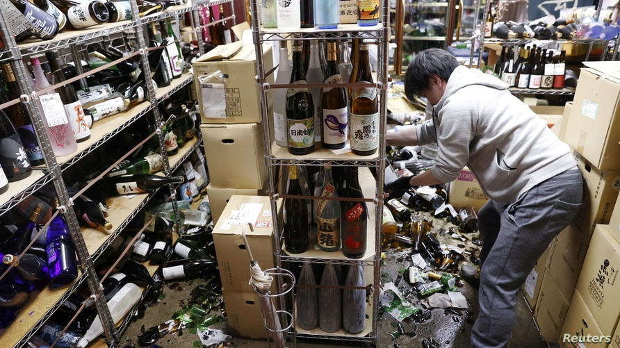 A worker cleans up broken bottles at a liquor shop after a strong quake in Fukushima, Japan, Feb. 13, 2021, in this photo taken by Kyodo.
