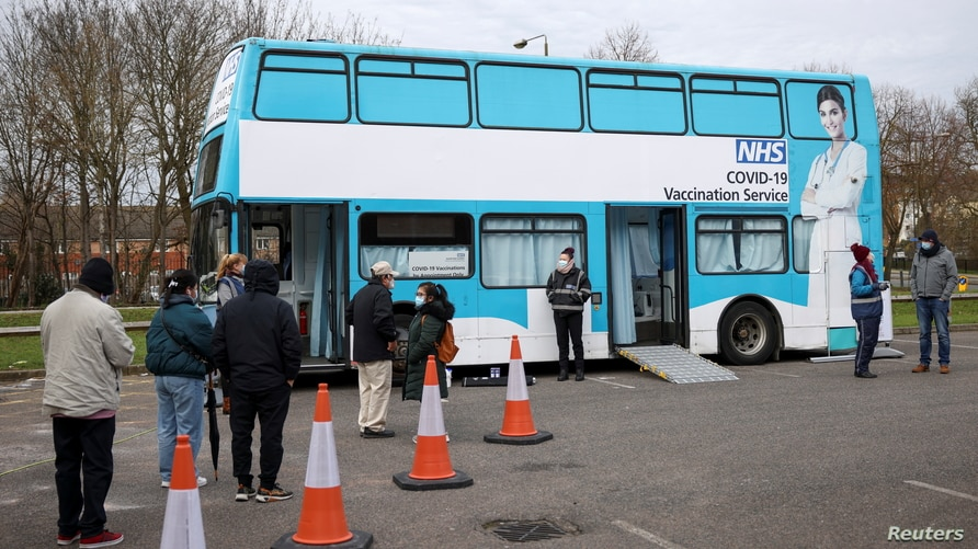 People queue outside a bus modified into a mobile vaccination centre for the coronavirus disease (COVID-19), in Thamesmead,…