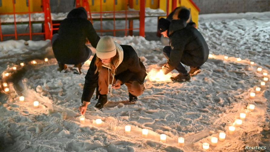 Supporters of Russian opposition politician Alexei Navalny, who was recently jailed for parole violations, arrange candles in…