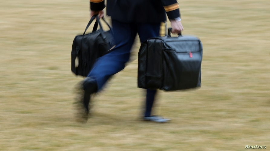 A White House military aide carrries the so-called nuclear football as he walks to board the Marine One helicopter with U.S…