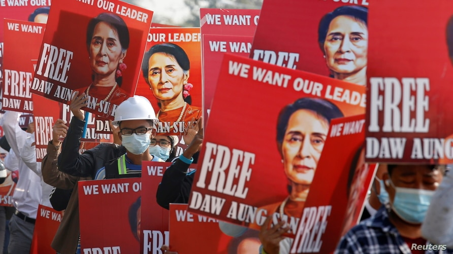 Demonstrators hold placards with the image of Aung San Suu Kyi during a protest against the military coup, in Naypyitaw,…