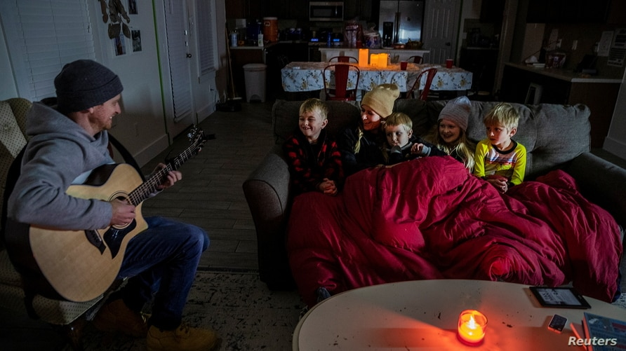 Brett Archibad, whose home was without electric power following winter weather, tries to entertain his family as they try to…
