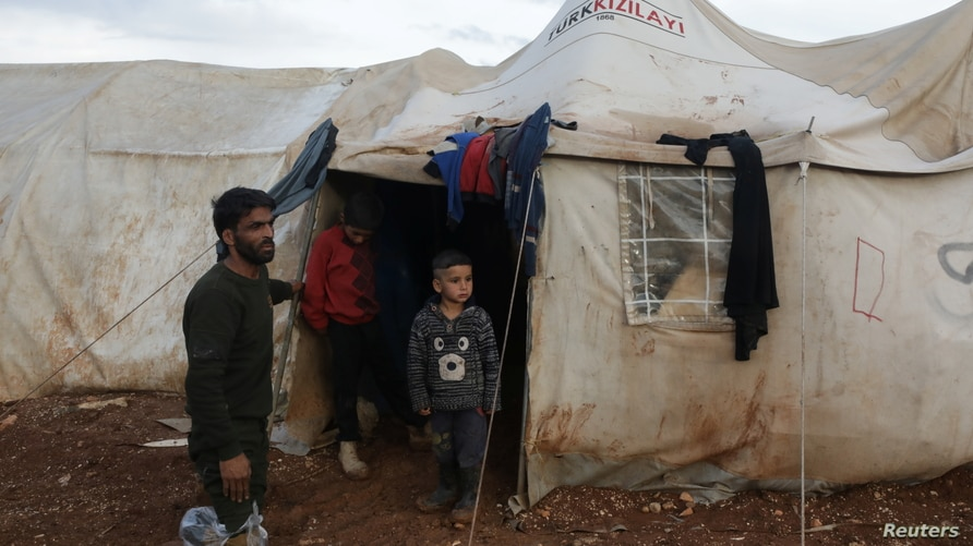 Ahmad Hamra, stands with his children outside a tent at an internally displaced Syrian camp, in northern Aleppo near the Syrian-Turkish border, Syria, Feb. 17, 2021.