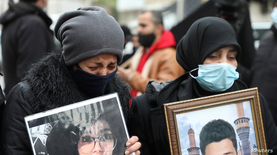 A relative of one of the victims of Beirut port explosion, reacts during a protest, after a Lebanese court removed the judge…