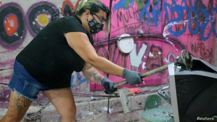 Luciana Holanda smashes a computer monitor at the Rage Room, a place where people can destroy everyday objects to vent their…