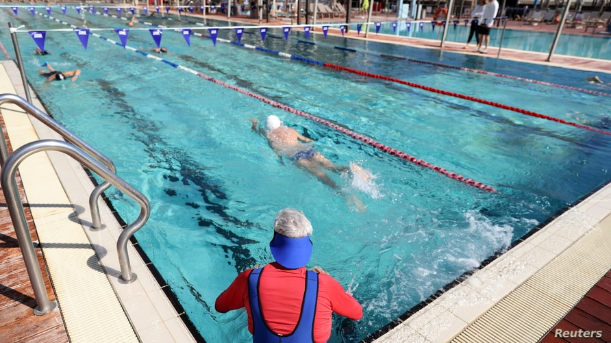 """People swim at a pool where a """"Green Badge"""" is required to enter, as Israel reopens swathes of its economy, continuing to lift…"""