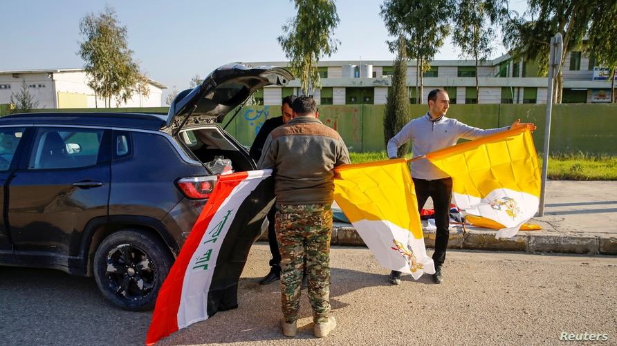 Christians volunteers hold Iraqi and Vatican flags as they decorate streets ahead of the planned visit of Pope Francis, in…