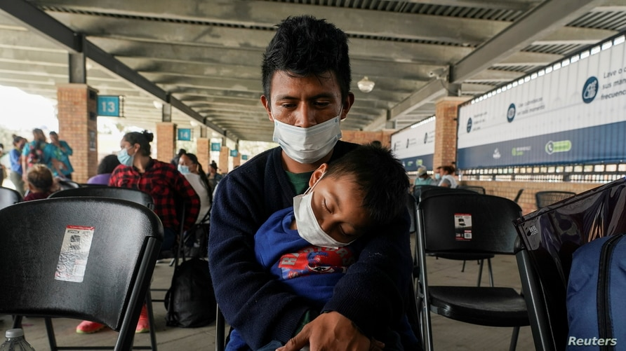 A migrant who crossed Gateway International Bridge from Mexico side to be processed to seek asylum in the U.S., waits with a…