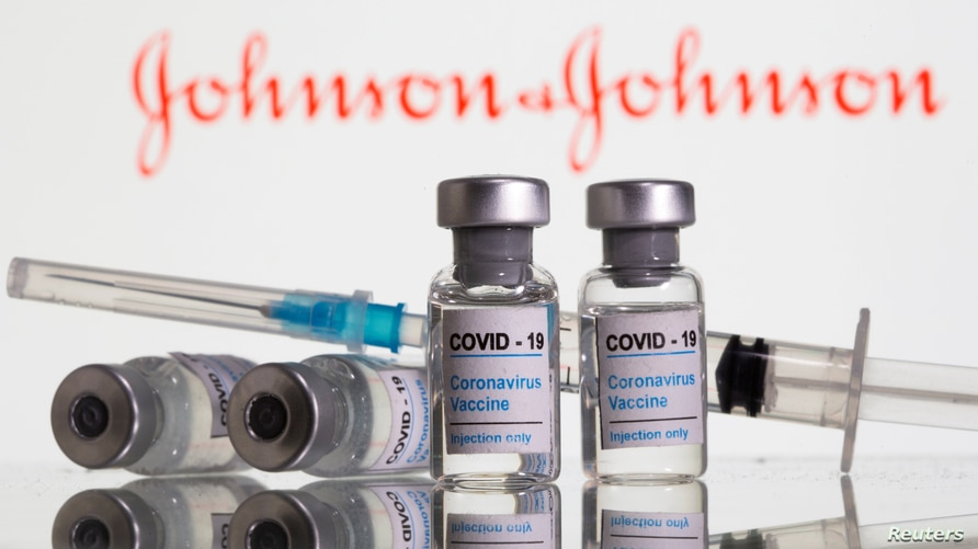 """FILE PHOTO: Vials labelled """"COVID-19 Coronavirus Vaccine"""" and syringe are seen in front of displayed Johnson & Johnson logo in…"""
