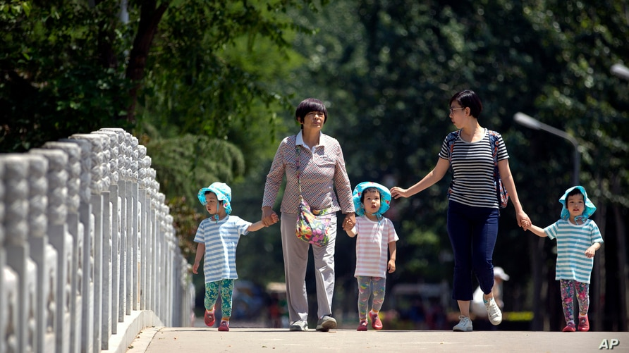 In this June 1, 2017 photo, women walk with children wearing matching hats as they cross a bridge at a public park on…