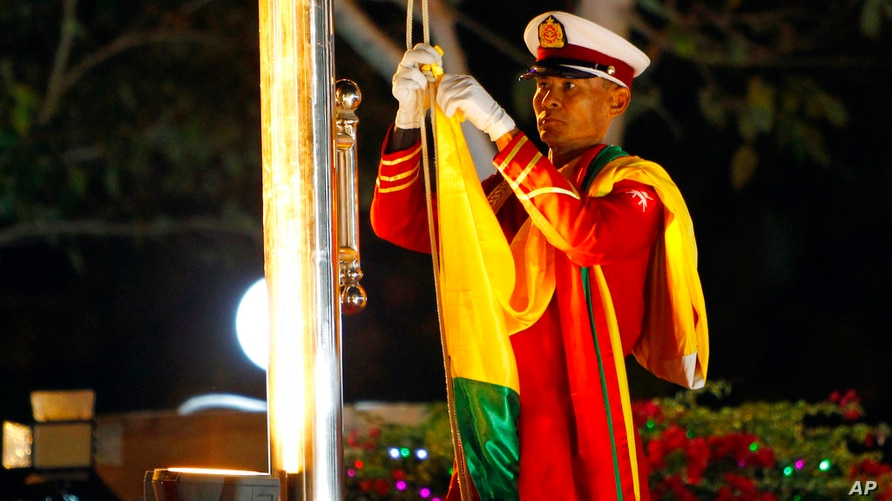 A Myanmar military soldier prepares to hoist a national flag during a ceremony to mark the 71st anniversary of its independence…