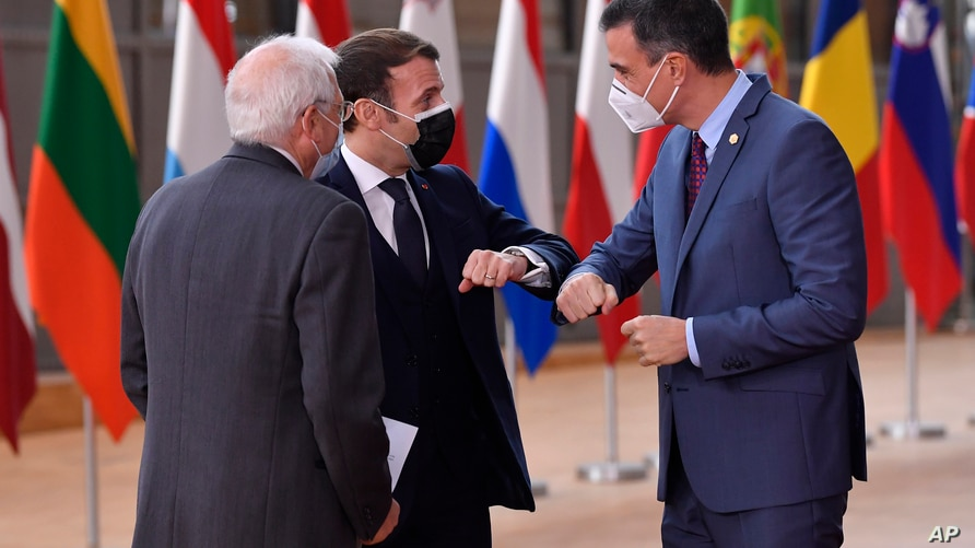 FILE - Spain's Prime Minister Pedro Sanchez, right, greets French President Emmanuel Macron, center, with an elbow bump during arrival for an EU summit at the European Council building in Brussels, Dec.10, 2020.