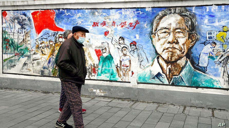"""Residents wearing masks past by a mural titled """"Memories""""on the eve of the anniversary of the 76-day lockdown in the central…"""