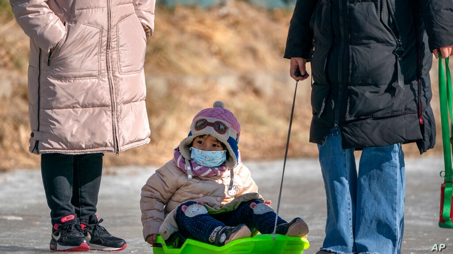 A child wearing a face mask to protect against the spread of the coronavirus is pulled in a sled across the surface of a frozen…