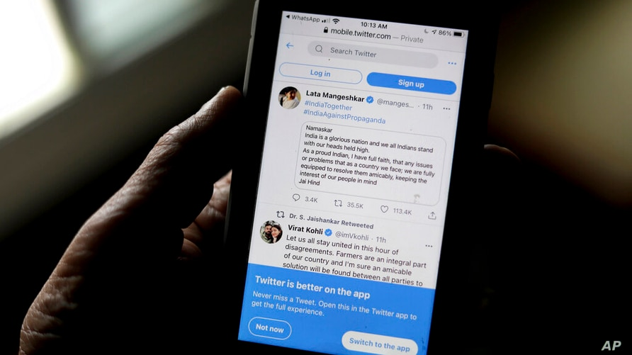 A man reads tweets by Indian celebrities, one of the many backing the Indian government, on his mobile in New Delhi, India,…