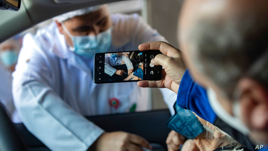 A man photographs his mother getting a shot of China's Sinovac CoronaVac vaccine for COVID-19 during a priority vaccination…