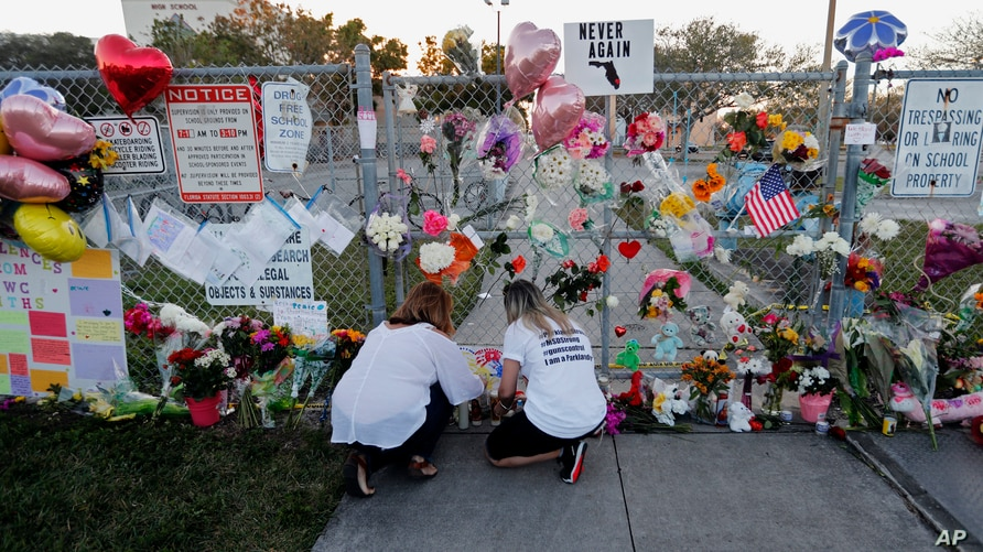 FILE - People light candles at a makeshift memorial outside Marjory Stoneman Douglas High School, where 17 students and faculty were killed in a mass shooting days earlier in Parkland, Fla.