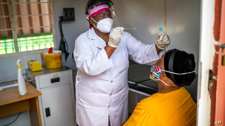 Asnath Masango, gives a patient a COVID-19 test at the Ndlovu clinic in Elandsdoorn, 200 kms north-east of Johannesburg Thursday Feb. 11, 2021. The center is running a study of the Johnson & Johnson COVID-19 vaccine.