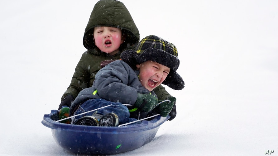 Two boys sled down an icy street Monday, Feb. 15, 2021, in Nolensville, Tenn. Much of Tennessee was hit with a winter storm…