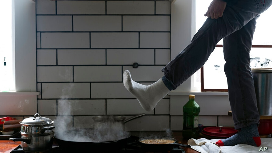 Jorge Sanhueza-Lyon stands on his kitchen counter to warm his feet over his gas stove Tuesday, Feb. 16, 2021, in Austin, Texas…