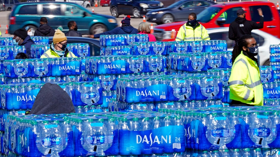 Water is loaded into cars at a City of Houston water distribution site Friday, Feb. 19, 2021, in Houston. The drive-thru…