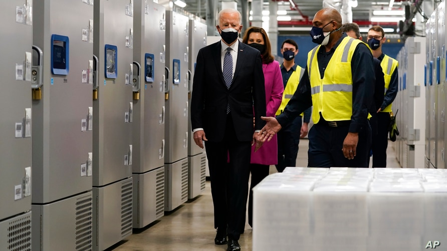 President Joe Biden walks past freezers used to store Pfizer-BioNtech's COVID-19 vaccine as he tours a Pfizer manufacturing site, Feb. 19, 2021, in Portage, Mich.