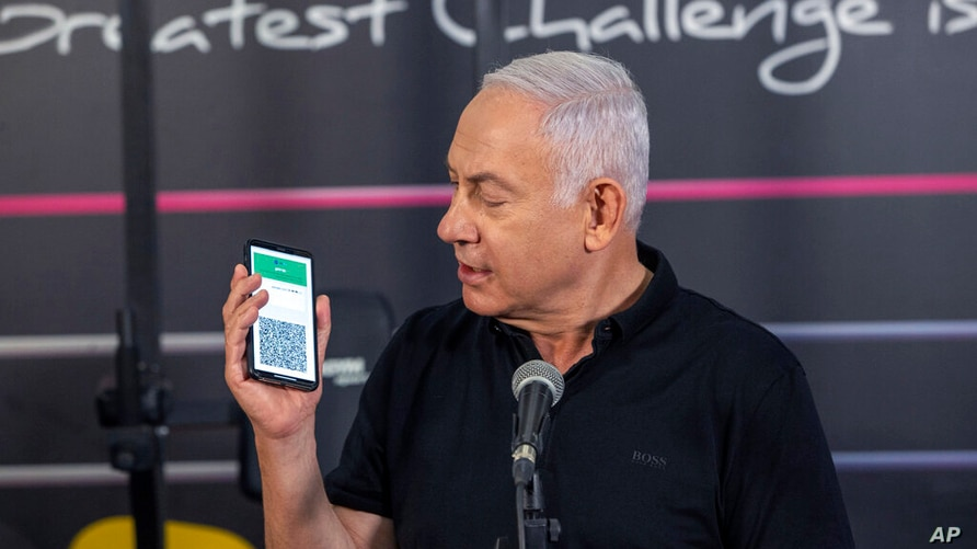 Israeli Prime Minister Benjamin Netanyahu talks to the media during a visit to the Fitness gym ahead of the re-opening of the…